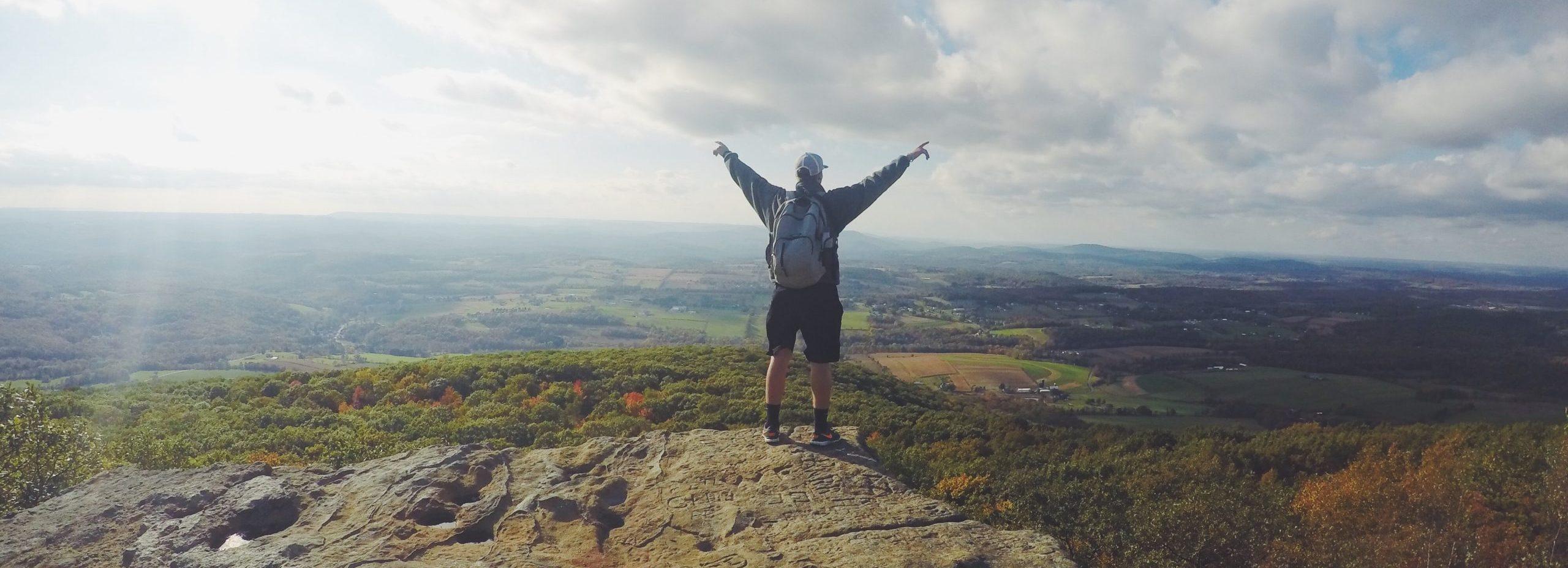 Mann steht auf Berg und hält gewinnend die Arme in die Luft